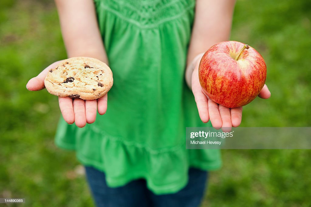 A girl holding a cookie and an apple : Stock Photo