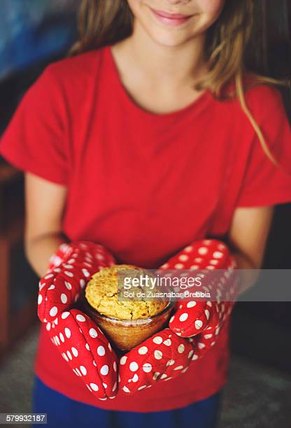 Girl holding a cupcake in her hands with oven mitt
