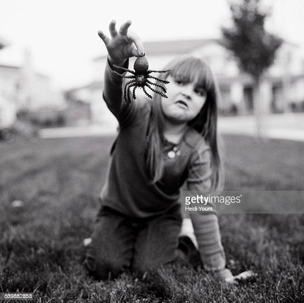 A girl holding a fake spider
