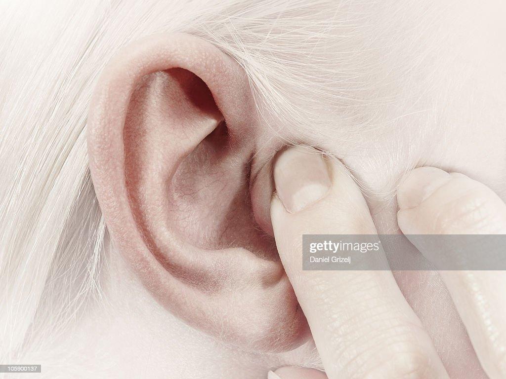 girl holding a finger over her ear : Stock Photo