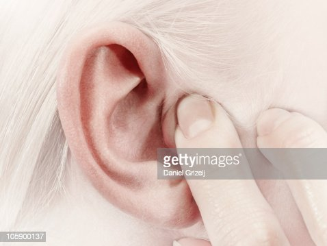 girl holding a finger over her ear : Stock Photo