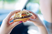 Girl holding a hamburger in  her hands sitting in a car. Unhealthy eating concept - shallow depth of field