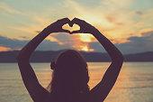 Girl holding a heart shape for the ocean / sea.