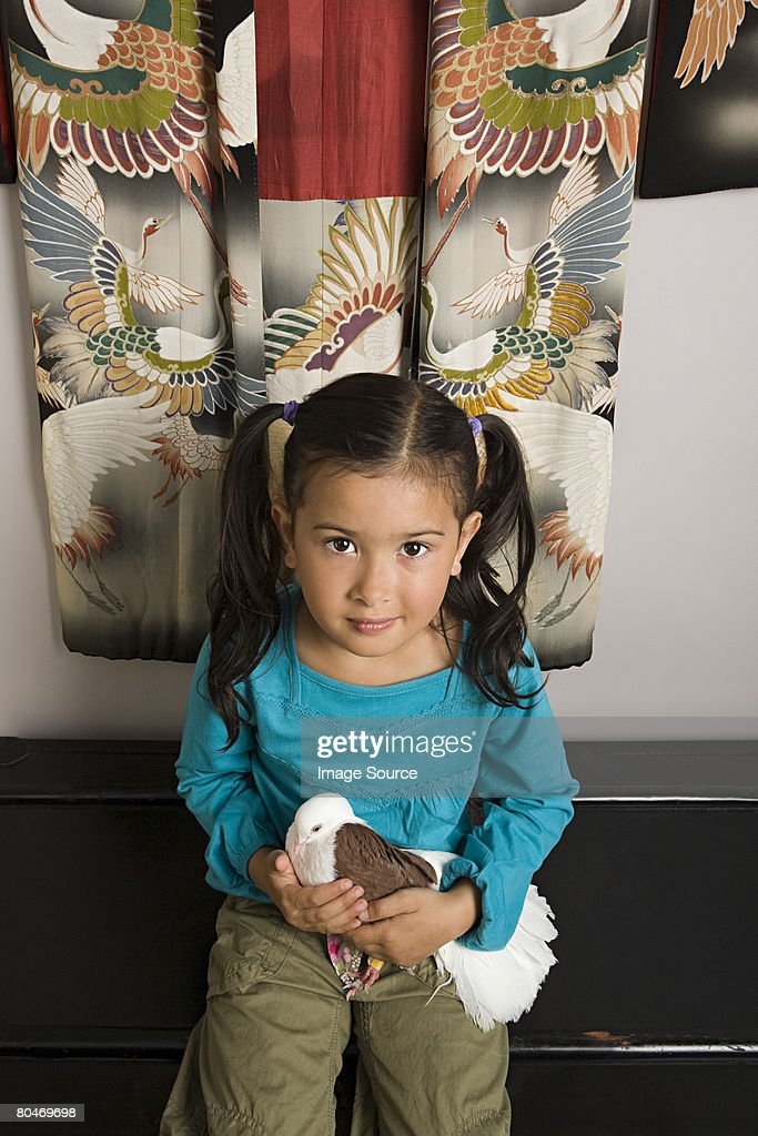 Girl holding a pigeon : Stock Photo
