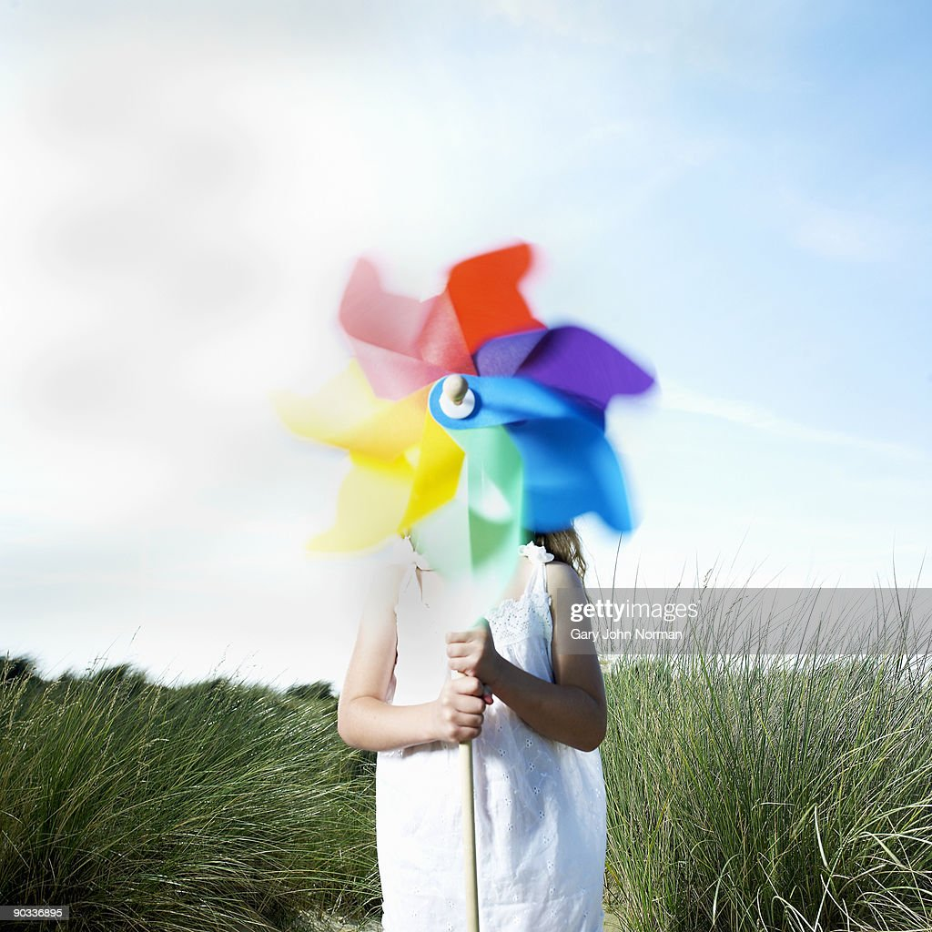 Girl Holding a Pinwheel in sea grass & sand dunes : Stock Photo