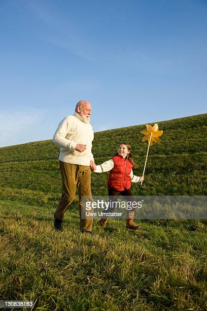 Girl holding a pinwheel running with her grandfather