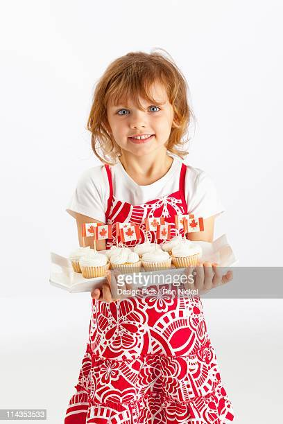 A Girl Holding A Plate Of Cupcakes