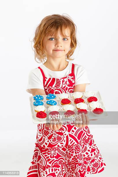 A Girl Holding A Platter Of Cupcakes