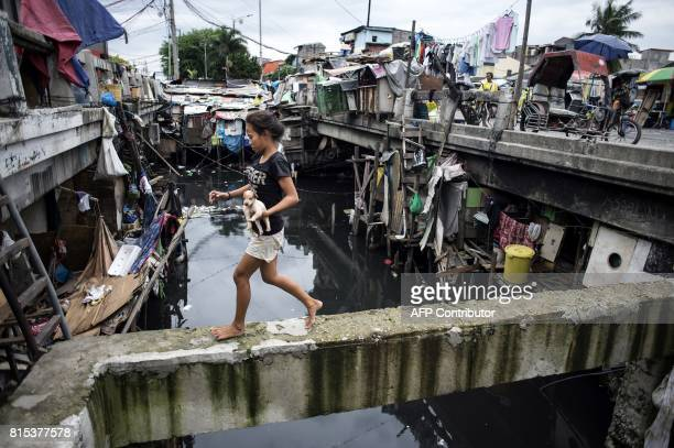 A girl holding a puppy crosses the Estero de Vitas in Tondo in Manila on July 16 2017 The Philippine economy has sustained one of the fastest growth...