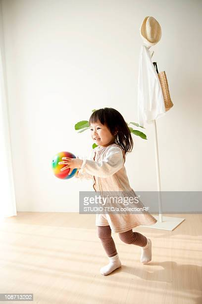 Girl holding a rubber ball and running
