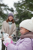 Girl Holding a snowman in a park with mother