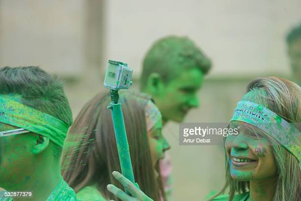 Girl holding a stick selfie wit GoPro taking selfies during a colorful powder celebration with green Gulal