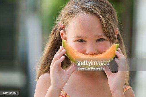 Girl holding a wedge of cantaloupe : Stock Photo