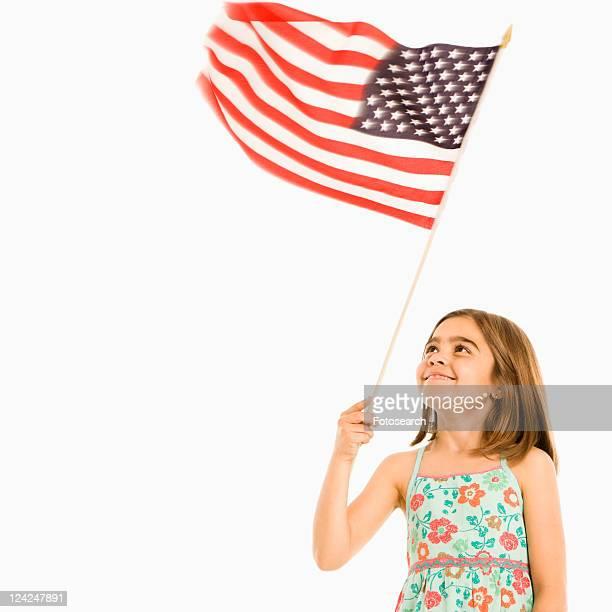Girl holding American flag against white background.