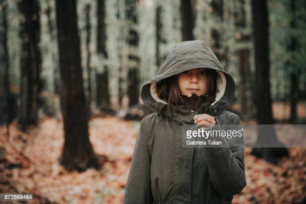 Girl holding an autumn leaf in the forest