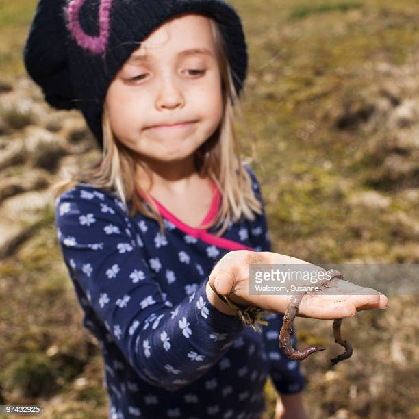 Girl holding an earthworm, Sweden.