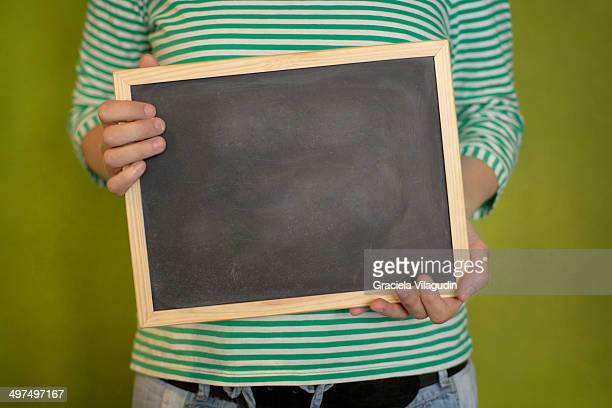 Girl holding an empty chalkboard