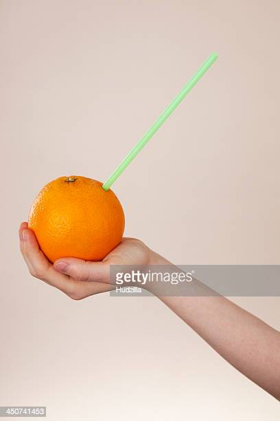 A girl holding an orange with a drinking straw in it, close-up of arm and hand