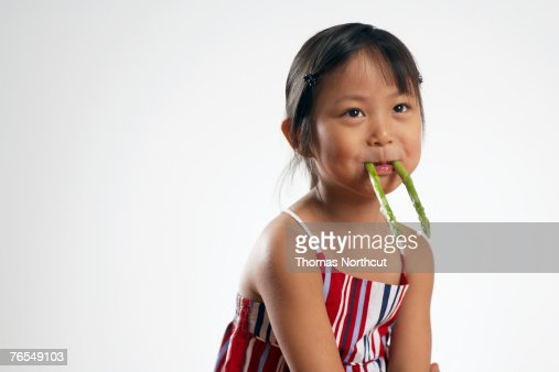 Girl (3-5) holding asparagus spears in mouth, smiling, close-up