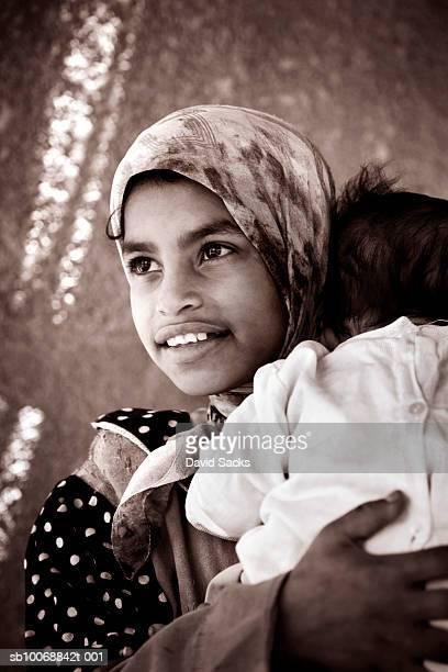 Girl (8-9) holding baby