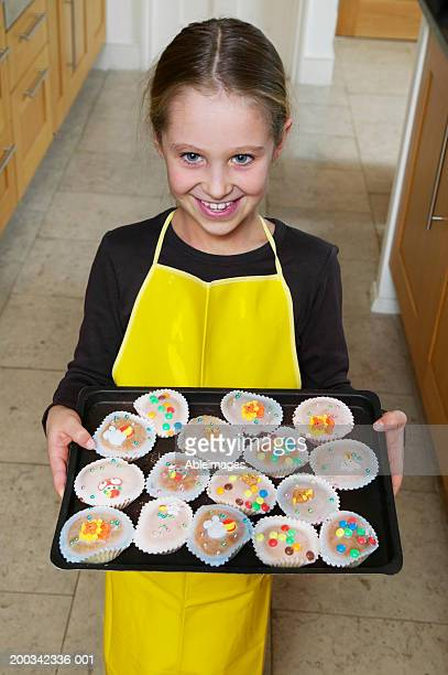 Girl (5-7) holding baking tray full of cupcakes, smiling, portrait