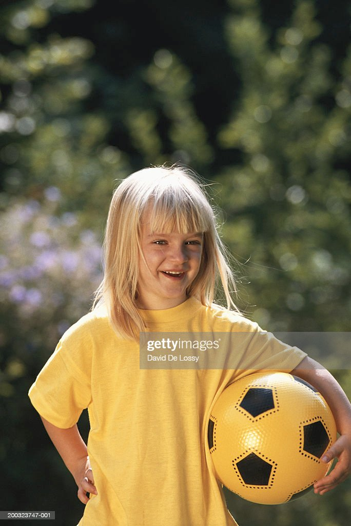 Girl (6-7) holding ball, smiling, portrait : Stock Photo