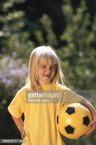 Girl (6-7) holding ball, smiling, portrait : Stock Photo