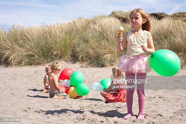 Girl holding balloon eating ice cream on beach, Wales, UK