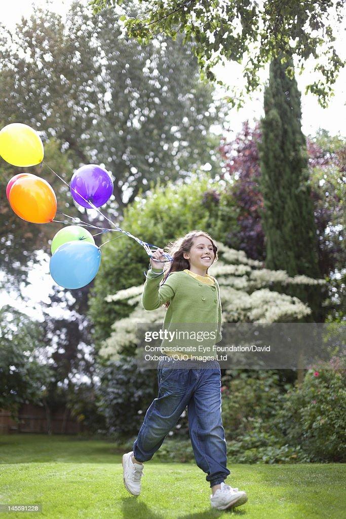 Girl (10-11) holding  balloons in garden : Stock Photo