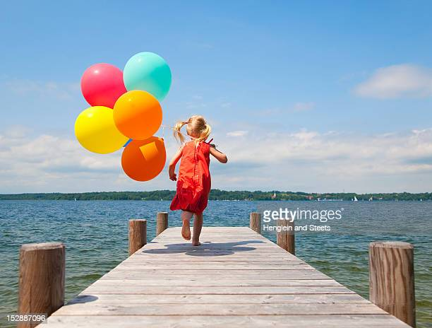 Girl holding balloons on wooden pier