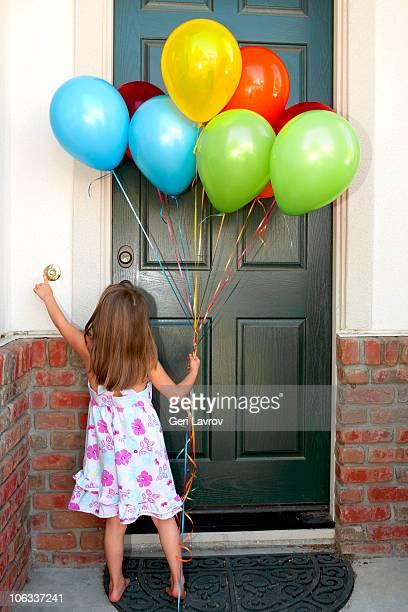 Girl holding balloons ringing a doorbell