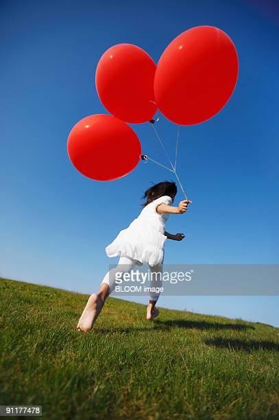 Girl holding balloons, running up hill, rear view