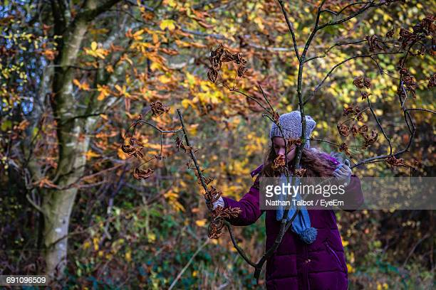 Girl Holding Bare Twig In Forest
