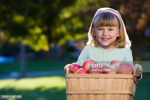 Girl (4-5) holding basket of apples, smiling, portrait