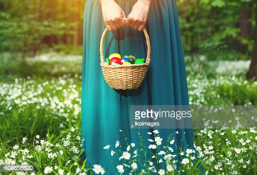 Girl holding Basket of easter eggs on meadow : Stock Photo