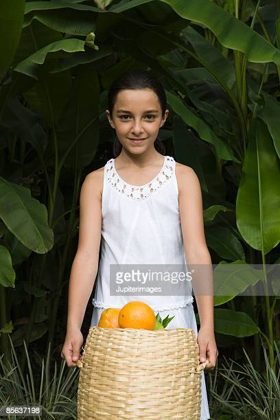 Girl holding basket of oranges , Colombia