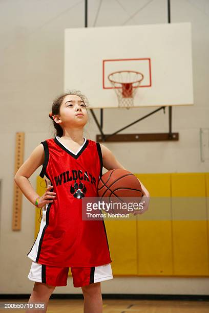 Girl (7-9) holding basketball on basketball court, looking up