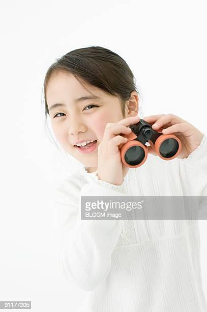 Girl holding binoculars, studio shot