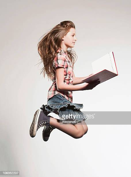 Girl (8-9) holding book and jumping, side view