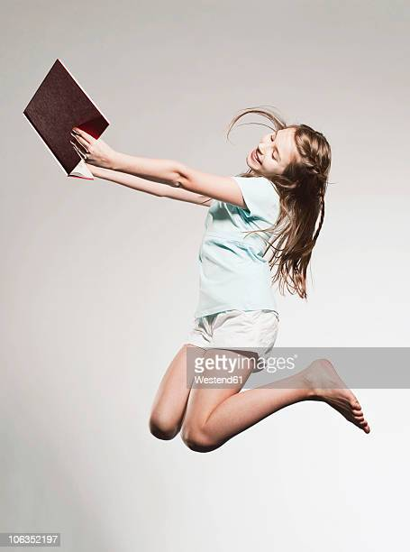 Girl (10-11) holding book and jumping, smiling