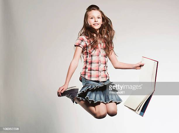 Girl (8-9) holding book and jumping, smiling, portrait
