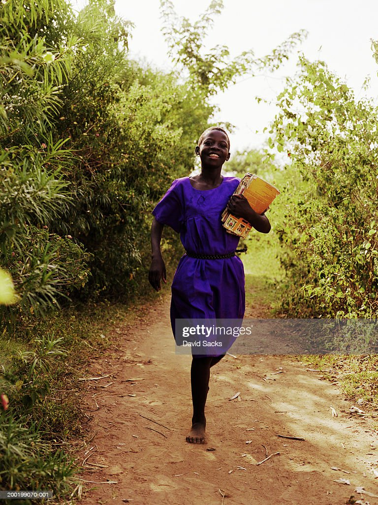 Girl (8-10) holding books, and running, smiling : Stock Photo