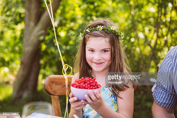 Girl holding bowl with redcurrants in garden