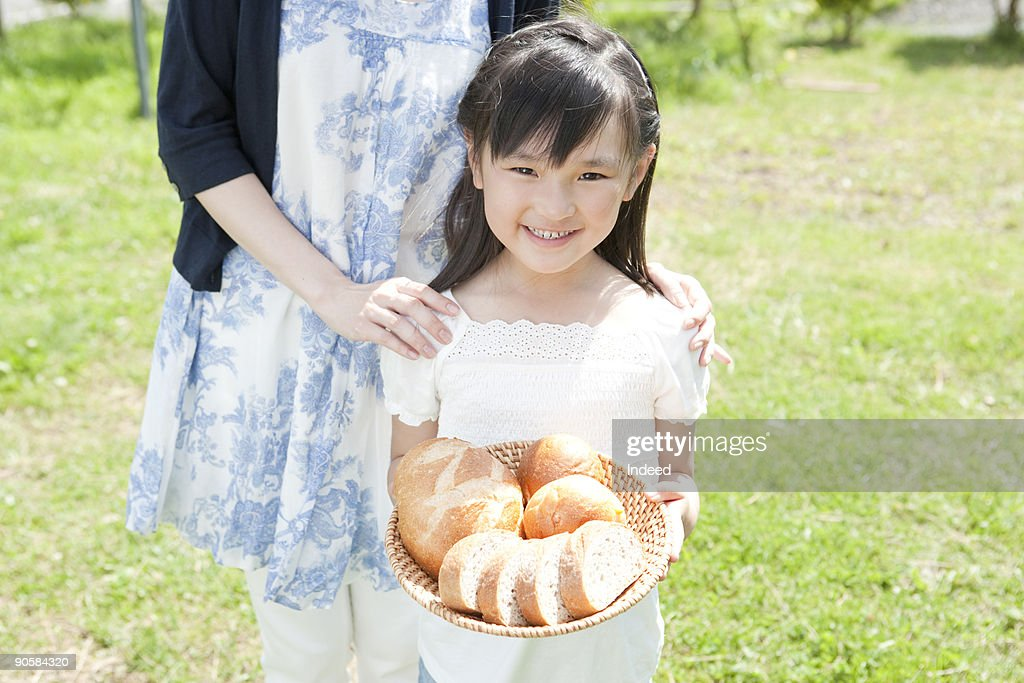 Girl (6-7) holding bread in basket next to mother : Stock Photo