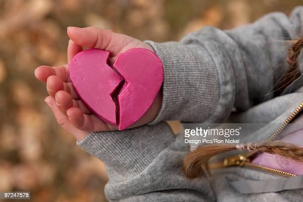 Girl holding broken heart