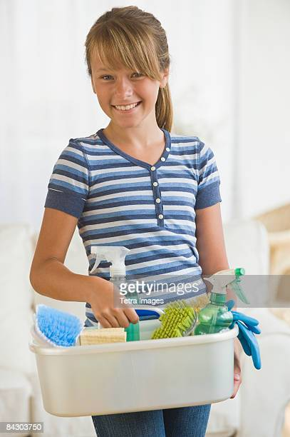 Girl holding bucket of cleaning supplies