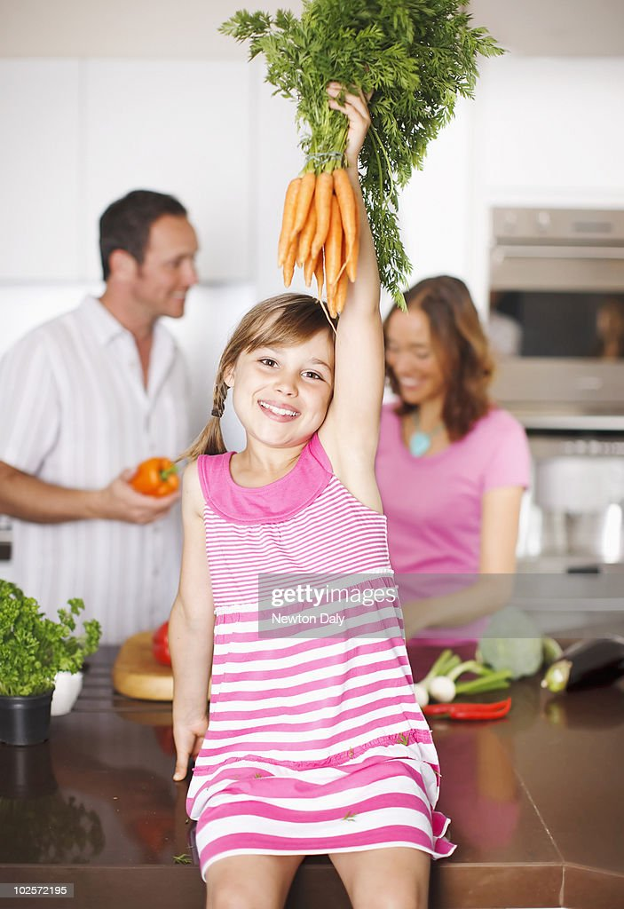 Girl (8-9) holding bunch of carrots, smiling : Stock Photo