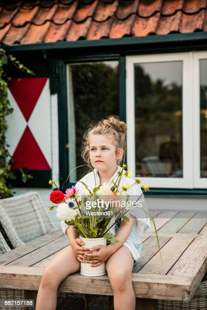 Girl holding bunch of flowers on terrace table