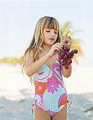 Girl (6-8) holding bunch of grapes on beach