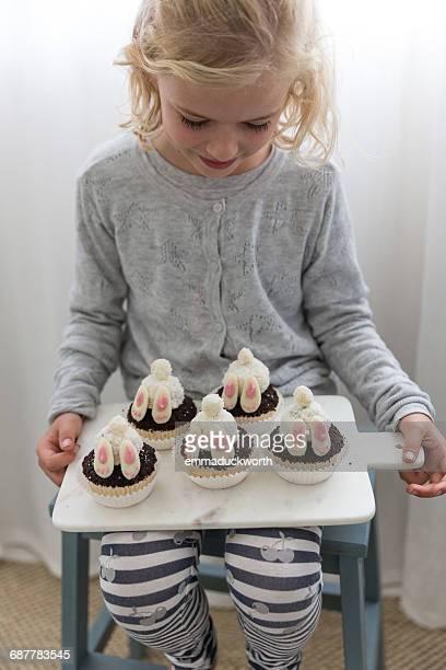 Girl holding bunny rabbit cupcakes